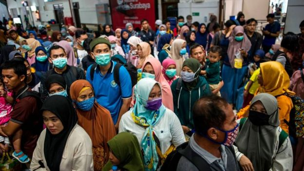 Indonesians wear九牧王官网 masks at transport hub.