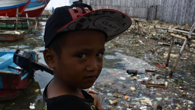 Niño frente a un basural de plástico.