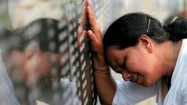 A family member of a Sri Lankan soldier who died in the civil war cries in front of a memorial