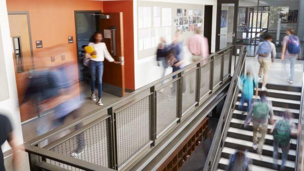 Vultos de alunos circulando entre portas, escadas e corredores de uma escola