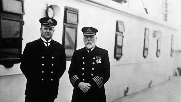 El capitán del Titanic, Edward Smith (der.). a bordo del barco, junto con el tripulante de cabina Hugh Walter McElroy.