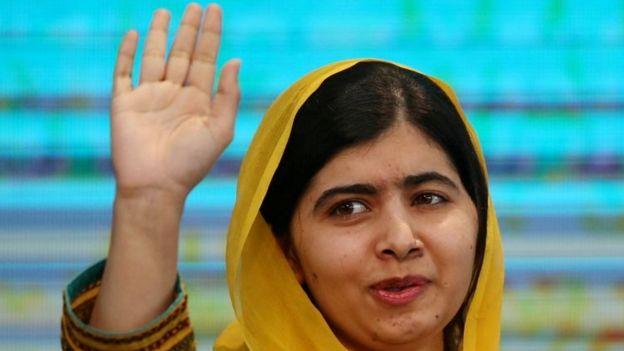 Malala acenando e sorrindo timidamente