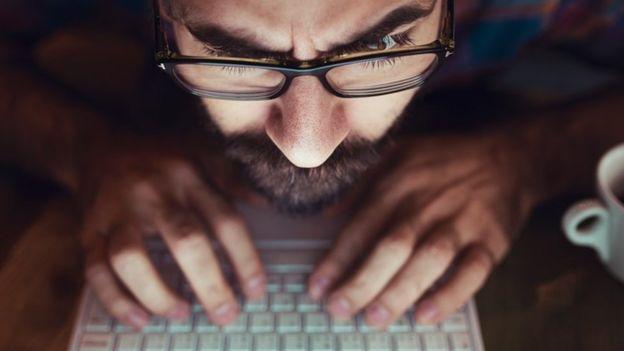 Una persona mirando muy de cerca su computador