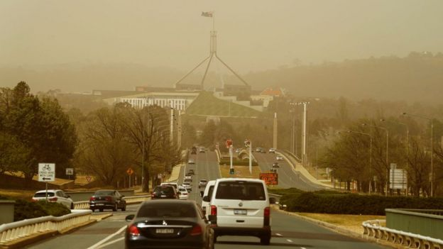 View of road leading to Parliament House shrouded by smoke from the city's fires on Thursday