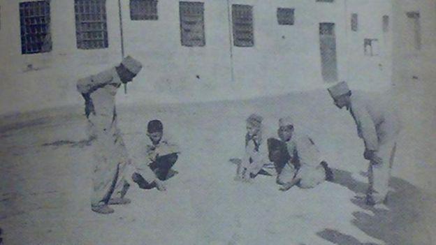 Crianças internas jogando bolinha de gude