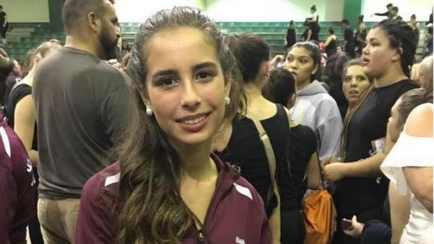 Uma adolescente olha diretamente para a câmera e sorri