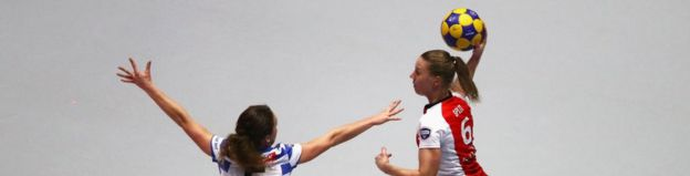 一名女子试图传球,另一名女子在荷兰足球联赛中阻挡她的路线
