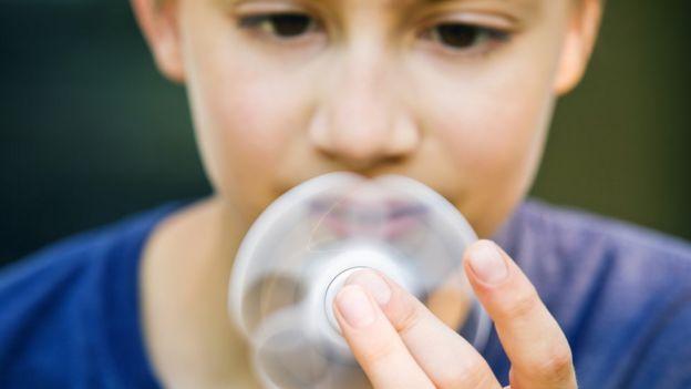 niño jugando fidget spinner