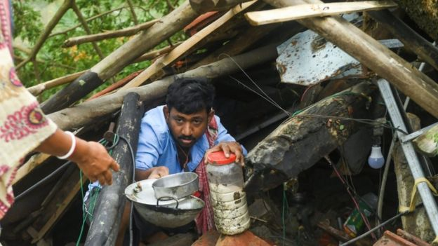 Una persona afectada por el ciclón intenta recuperar algunas pertenencias de su casa devastada en Bangladesh.