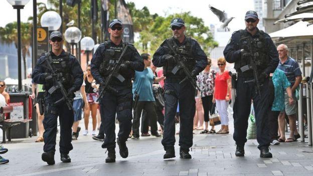 Heavily armed police officers walk along a street in Sydney