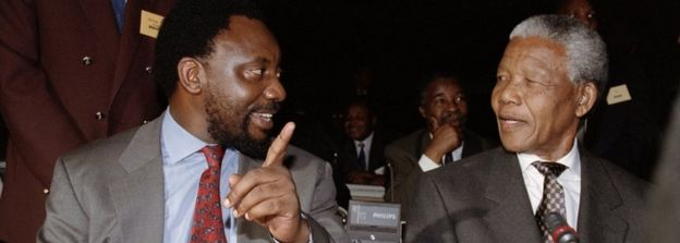 ANC Secretary General Cyril Ramaphosa (L) chats with Nelson Mandela after arrival at the world Trade Center, in Kempton Park 18 November 1993, where political leaders formally endorsed a constitutional blueprint that will end 300 years of white minority rule.