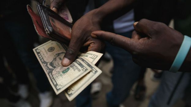 A person holding US dollars in Zimbabwe