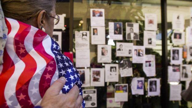 Mulher com bandeira americana observa mural com fotos das vítimas do 11 de setembro