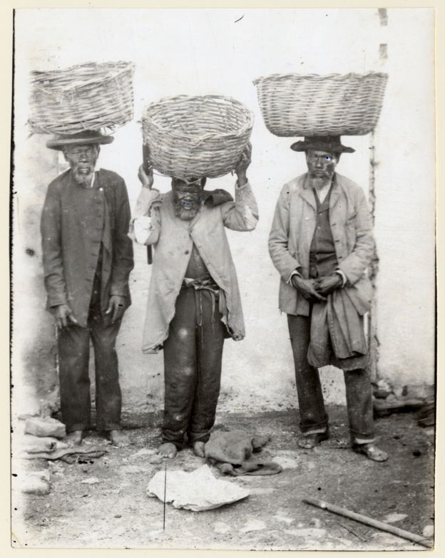Imagem mostra três homens, ex-escravos, com cestos equilibrados na cabeça. Eles trabalhavam como vendedores ambulantes em Porto Alegre, no final do século 19. Crédito: Acervo do Museu de Porto Alegre Joaquim Felizardo/Autor Desconhecido