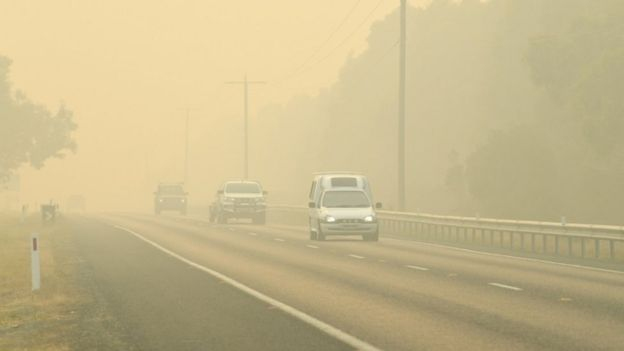 Cars evacuate through thick fog caused by fires in Victoria