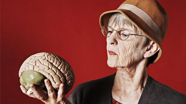 Mujer con un cerebro plástico en la mano
