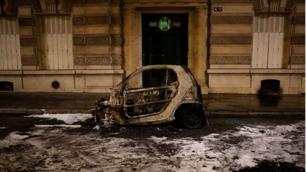 "A vandalised, burnt car is seen after clashes at a demonstration by the ""yellow vests"" movement in Paris, 8 December"