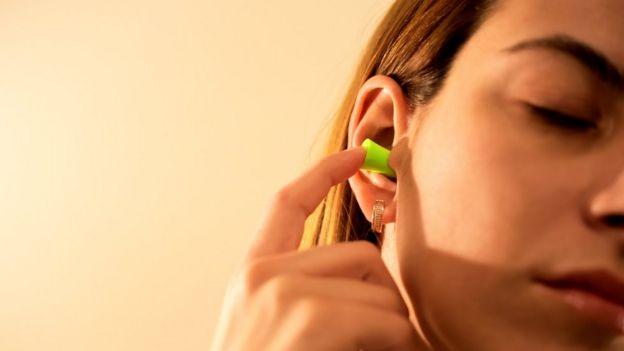 Woman putting ear plugs in