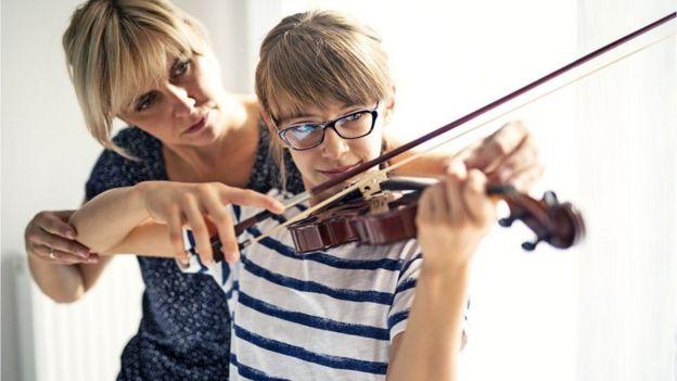 menina aprendendo a tocar violino com professora