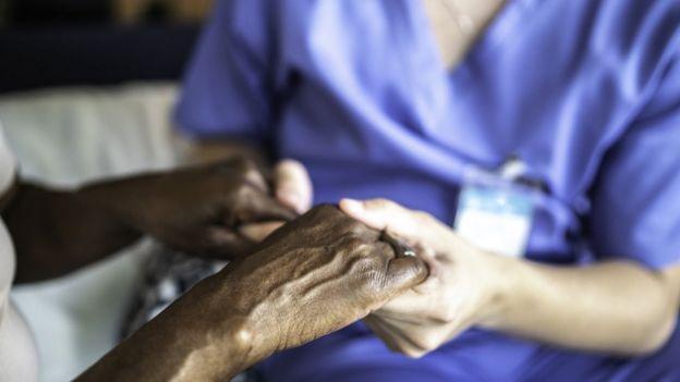 Mãos de paciente e enfermeira juntas