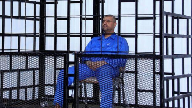 Libyalı lider Muammer Kaddafi'nin oğlu Saif el-İslam Kaddafi, 25 Mayıs 2014'te Zintan'da bir mahkeme salonunda barların ardındaki duruşmaya katıldı