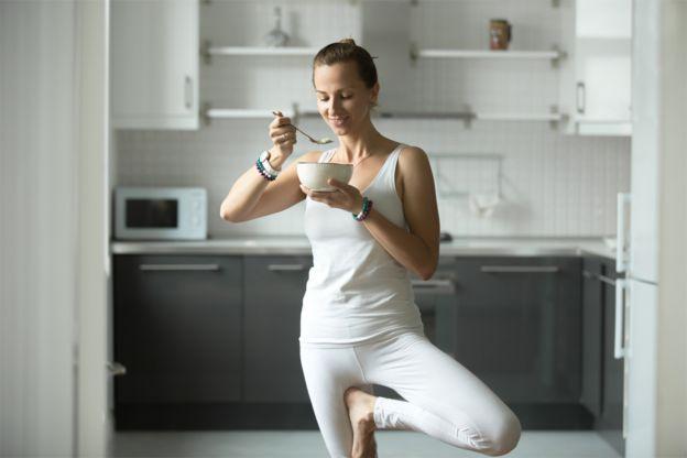 Una mujer parada en una pierna mientras come.