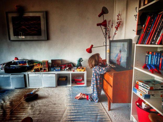 طفلة أمام شاشة تلفاز