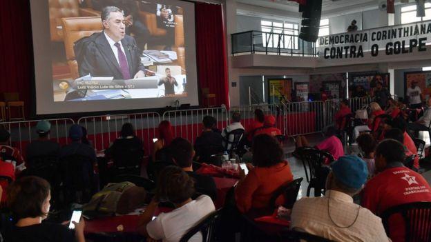 Militantes del partido de Lula miran el juicio.