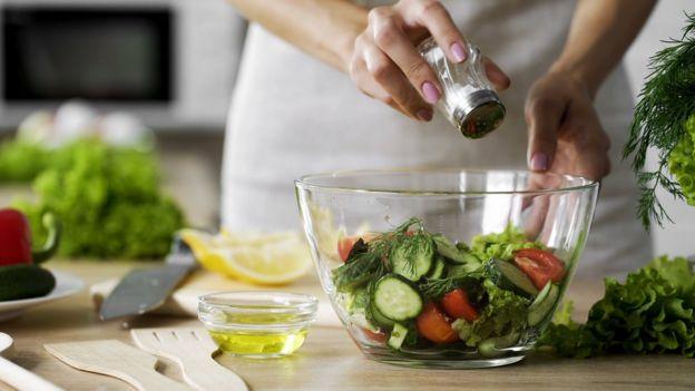 Mão de mulher segurando saleiro e salgando salada