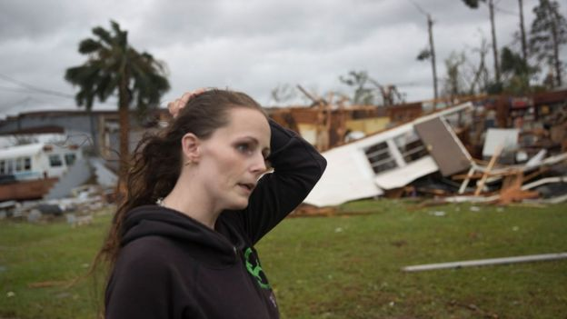 Haley Nelson stands in front of what is left of one of her father's trailer homes after hurricane Michael passed through the area, 10 October 2018
