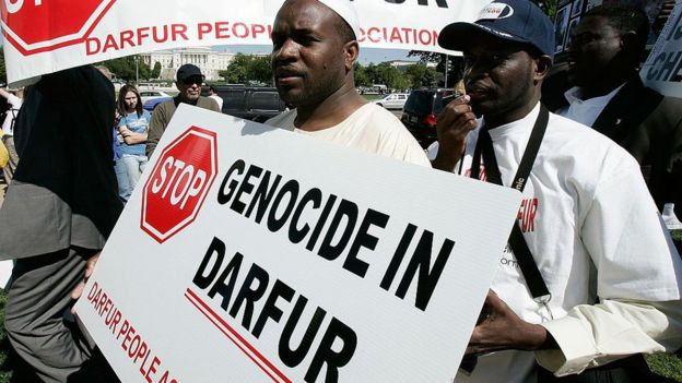"Man holding a sign saying ""Stop genocide in Darfur"""