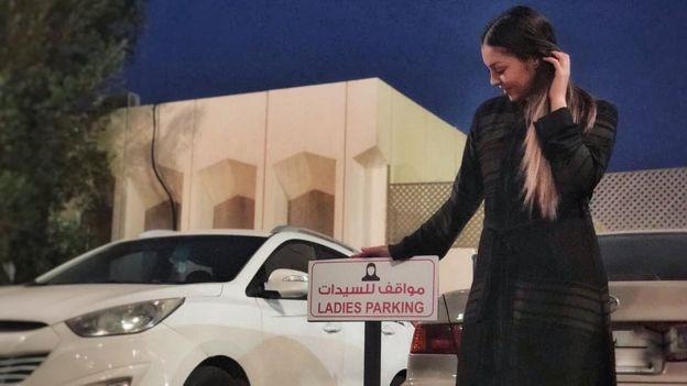 Gabriela perto de placa sinalizando placa de estacionamento para mulheres