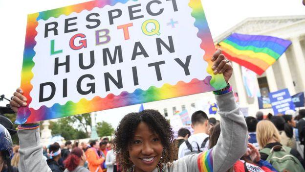 Una joven con una pancarta que pide respeto para la dignidad humana de la comunidad LGBTQ