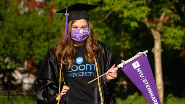 A student wears a protective face mask, graduation cap and graduation gown in Washington Square Park during the coronavirus pandemic on May 15, 2020
