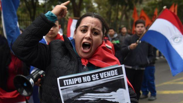 """Manifestante com cartaz exibindo foto de hidrelétrica e dizeres: """"Itaipu não se vende, Itaipu se defende"""""""