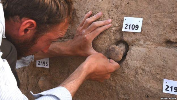 Tello antik kentindeki tapınağı inceleyen arkeologlar duvarlarda çalışmalar yürütüyor.