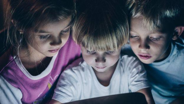 Foto mostra três crianças olhando para um tablet à noite