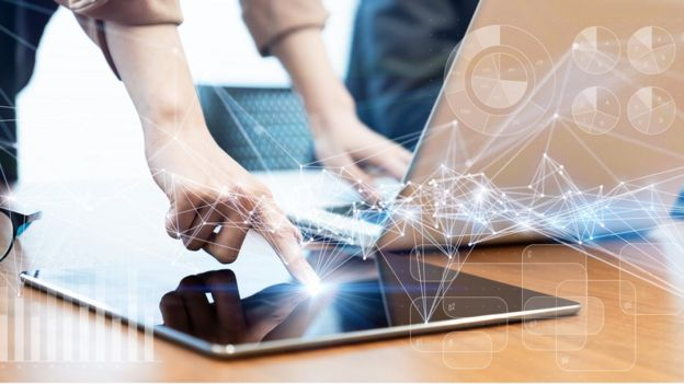 Mão toca em tablet ao lado de laptop na mesa, com ilustração sobreposta de redes e gráficos