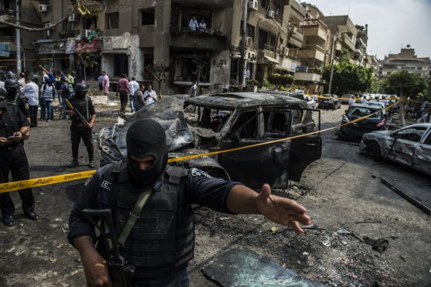 Egyptian security forces stand guard at the site of a bomb attack that targeted the convoy of Egyptian state prosecutor, Hisham Barakat, who died hours after the powerful explosion hit his convoy, in the capital Cairo on June 29, 2015.