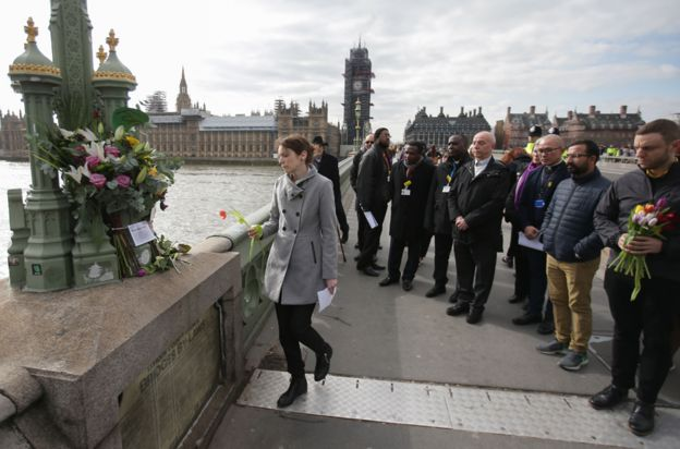 Hospital staff leave flowers on Westminster Bridge on the anniversary of the attack