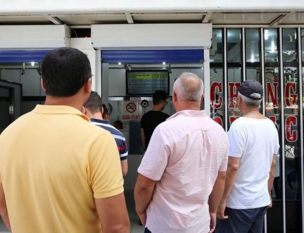 Turks in Ankara examine the fluctuating exchange rate at a currency exchange shop