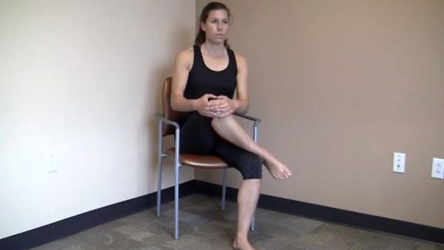 Mujer sentada con un tobillo encima de la rodilla de la otra pierna (captura de pantalla de un video de YouTube).