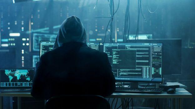 Hacker delante de varias computadoras.