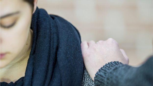 Pessoa coloca mão no ombro de mulher