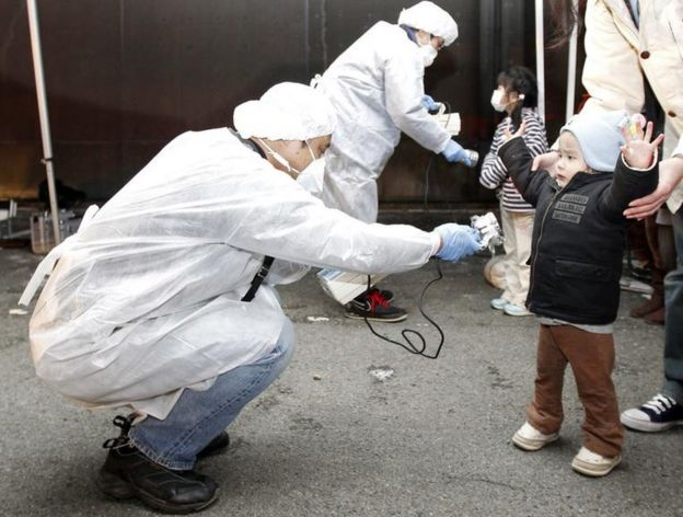 Officials in protective gear check for signs of radiation on children from the evacuation area near the Fukushima plant in March, 2011