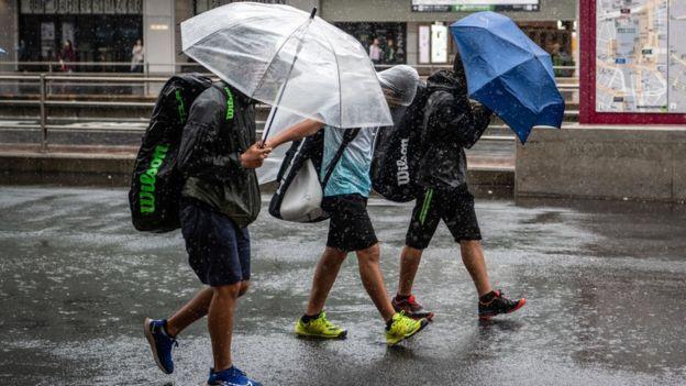 Three people walking to Shinjuku station in Tokyo