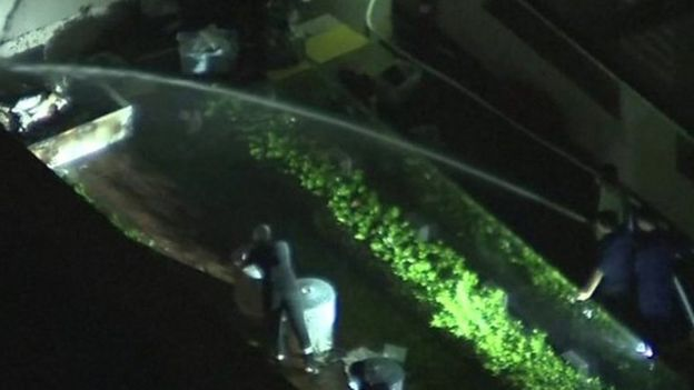 People spraying water on object outside of consulate and man closing rubbish bin