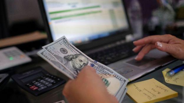 Dólares y laptop