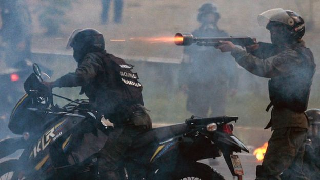 Policeman fires rubber bullet during a 2019 protest in Venezuela