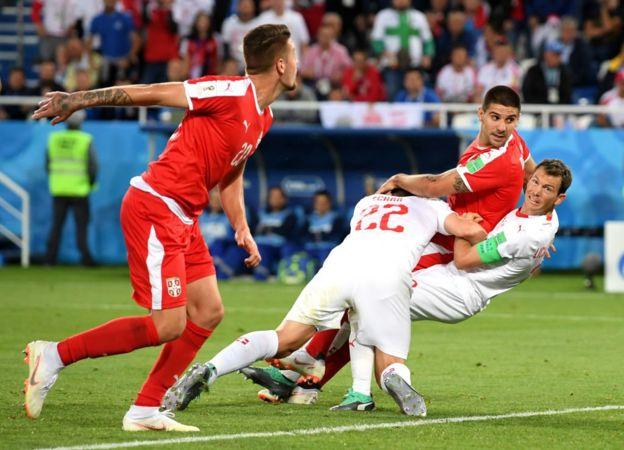 Stephan Lichtsteiner y Fabian Schaer tumban a Aleksandar Mitrovic en el área, en el partido de Serbia contra Suiza en Rusia 2018